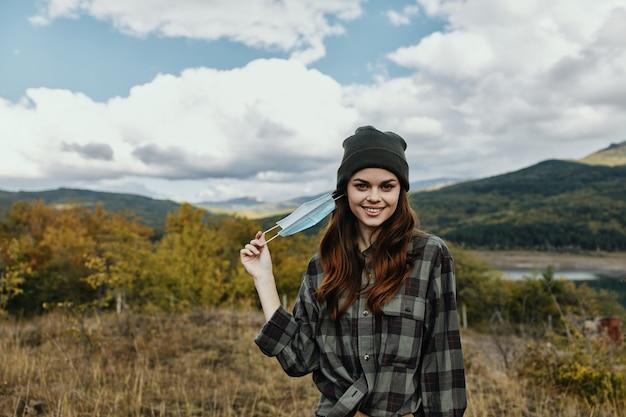Donna felice in una camicia a quadri nella foresta di autunno con una mascherina medica sul viso.