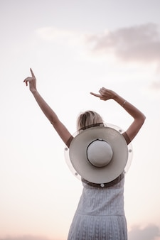 Una donna felice posa contro il cielo foto di una bellissima giovane bionda con le mani alzate in un ...