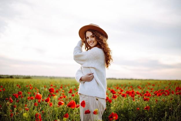 Donna felice in posa in un campo di papaveri