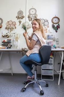 Donna felice in posa con piuma di pavone in officina che crea acchiappasogni usa materiale naturale