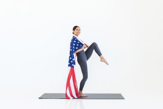 Donna felice che pratica yoga stando in piedi sul tappetino con la bandiera americana