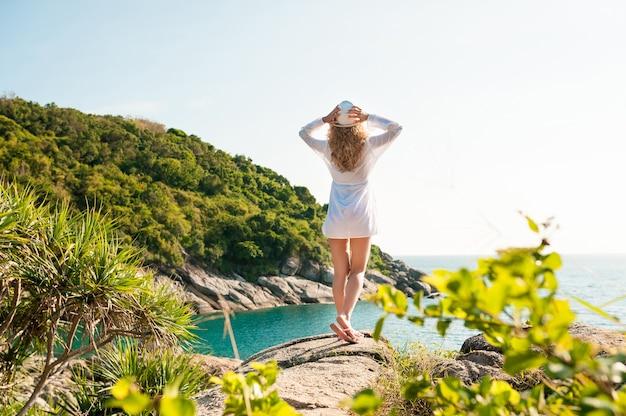 Donna felice che alza le braccia e si gode la libertà in spiaggia in una giornata di sole.