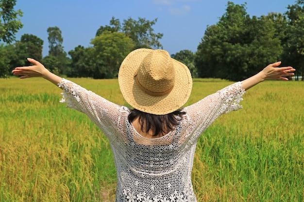 Donna felice che alza le sue braccia nella risaia piena di piante di riso mature pronte per la raccolta