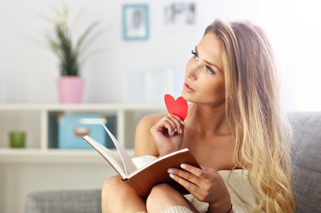 Donna felice che legge sul divano