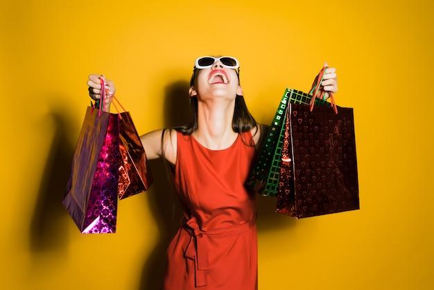 Donna felice in vestito rosso che tiene le borse della spesa