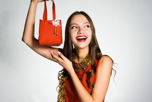 La donna felice in vestito rosso tiene in mano una piccola borsetta