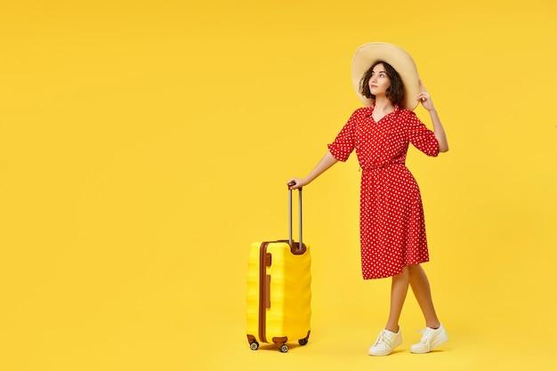 Donna felice in vestito rosso con la valigia che va in viaggio su sfondo giallo. copia spazio