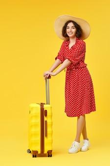 Donna felice in vestito rosso con la valigia che va in viaggio su sfondo giallo.