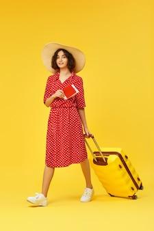 Donna felice in abito rosso con valigia e passaporto che viaggiano su sfondo giallo.