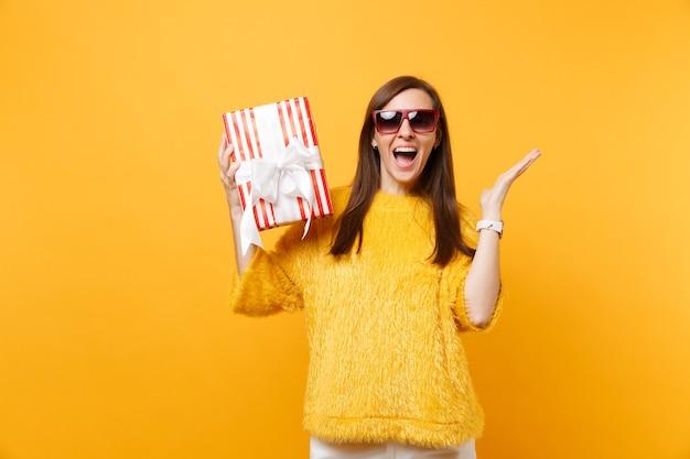 Donna felice in occhiali rossi allargando le mani tenendo la scatola rossa con regalo presente celebrando godendo la vacanza isolato su sfondo giallo brillante. persone sincere emozioni, stile di vita. zona pubblicità.