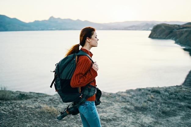 Donna felice in un maglione rosso con uno zaino sulla schiena che riposa nella natura vicino al mare e alle montagne in lontananza. foto di alta qualità