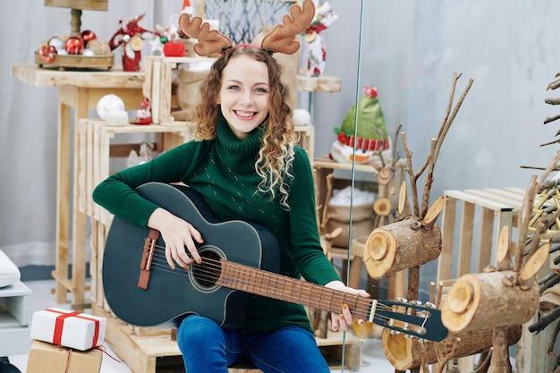 Donna felice in corna di renna a suonare la chitarra