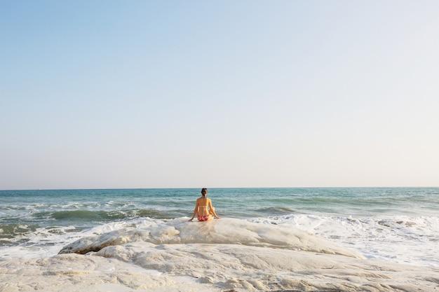 Donna felice che si distende su una spiaggia perfetta del mare