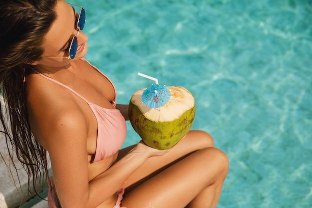 Donna felice che si distende in piscina e beve acqua di cocco