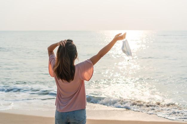 Donna felice che si rilassa con la maschera chirurgica sulla mano in spiaggia. nuovo concetto di stile di vita normale
