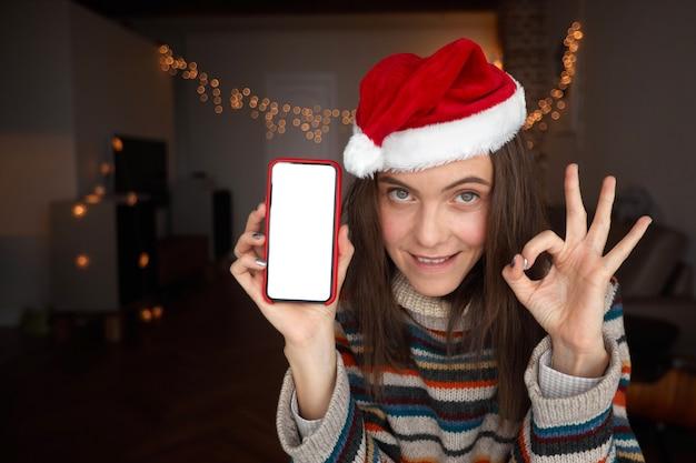 Donna felice in cappello della santa dimostrando smartphone con schermo vuoto e gesticolando ok durante la celebrazione del natale a casa