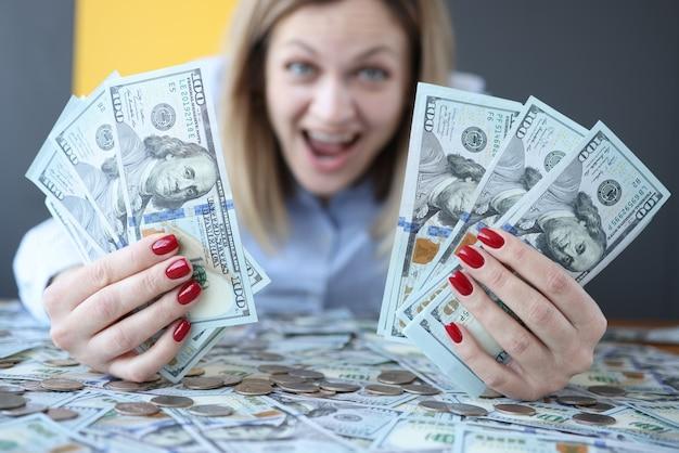 Donna felice che grida e che tiene molti soldi nel suo primo piano delle mani. vincere alla lotteria