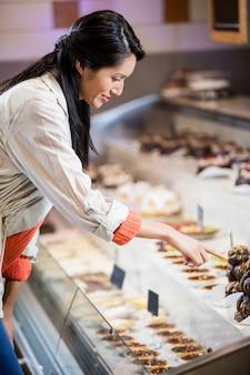 Donna felice che seleziona i dessert