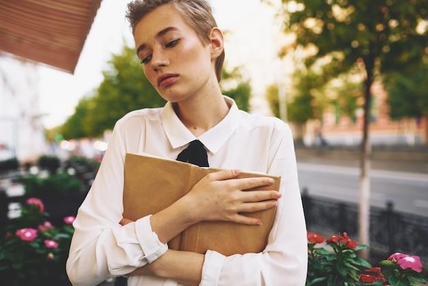 Donna felice in camicia capelli corti modello libro caffè ristorante alberi di strada