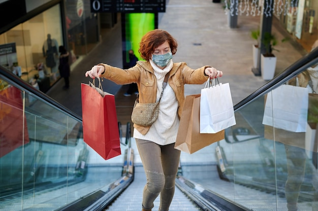 Donna felice che fa shopping in un centro commerciale con maschera facciale, new normal, covid-19