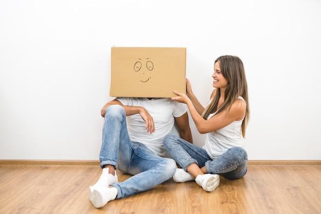 La donna felice si siede vicino all'uomo con una scatola di cartone sulla testa
