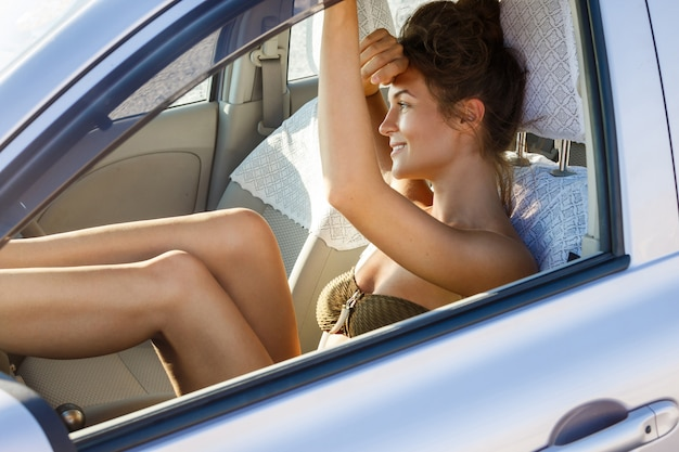 Donna felice che si siede in macchina