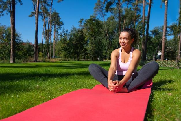Felice donna seduta su un tappetino fitness, godendo di allenamento in una soleggiata giornata estiva