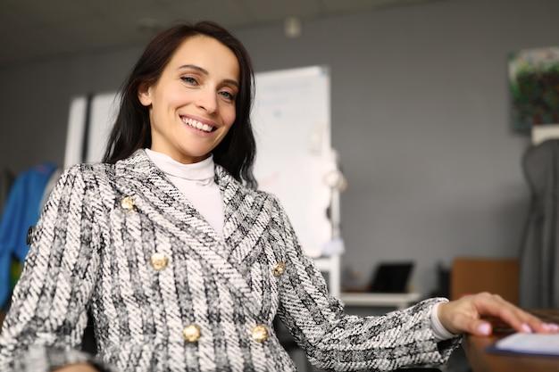 Donna felice che si siede nell'ufficio alla tavola e nel sorridere