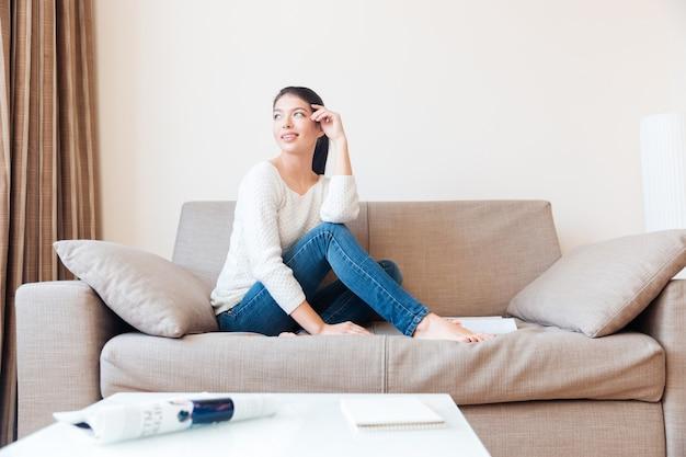 Donna felice seduta sul divano e distoglie lo sguardo dalla finestra