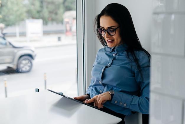 Donna felice seduta a tavola e guardando il tablet