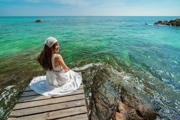 Felice donna seduta su un ponte di legno nella spiaggia del mare a koh munnork island, rayong, thailandia