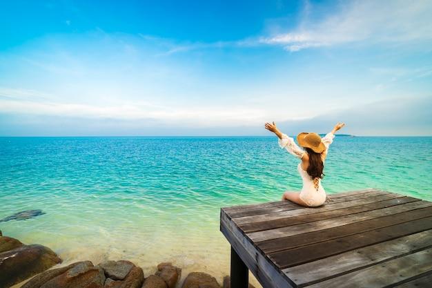 Felice donna seduta su un ponte di legno con il braccio alzato in mare a koh munnork island, rayong, thailandia