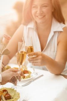 La donna felice sorride tenendo il bicchiere di vino bianco. le coppie mature hanno l'evento all'aperto al caffè della spiaggia.