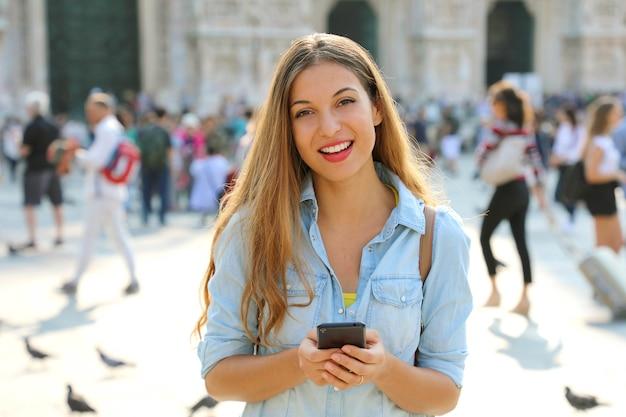 Donna felice che sorride e che cammina per strada utilizzando uno smartphone