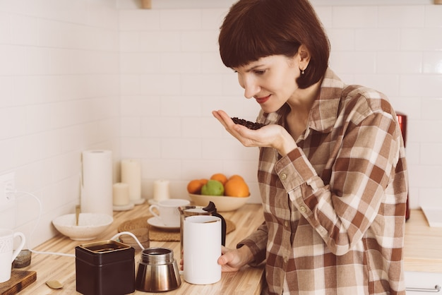 Donna felice che annusa caffè dalla lattina e odore di aroma. fagioli freschi di inalazione femminile