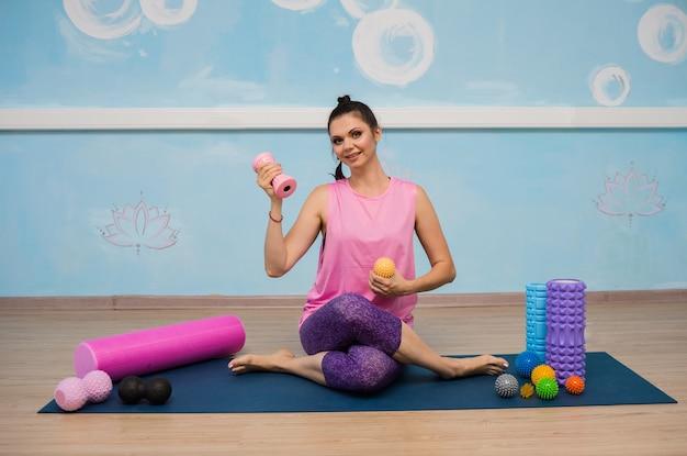 Una donna felice in abiti sportivi è seduta con massaggiatori ortopedici e palline sul tappeto