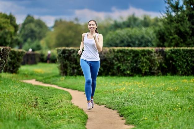 La donna felice in abiti sportivi sta correndo sul sentiero nel parco