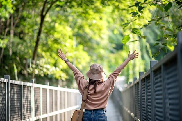 Donna felice allargando le braccia nel sentiero natura.