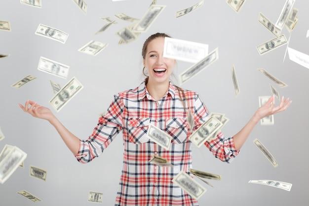 Donna felice in piedi sotto la pioggia di soldi