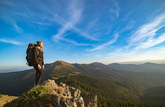 La donna felice in piedi sulla montagna soleggiata