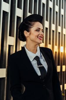 Hostess donna felice in uniforme in posa sullo sfondo della costruzione