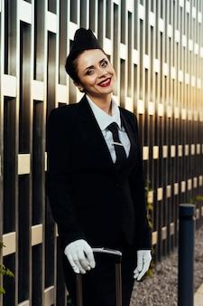 Hostess di donna felice in uniforme che posa alla macchina fotografica