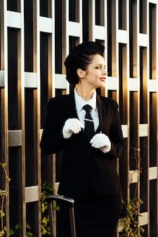 La hostess felice della donna in uniforme sta accanto alla valigia