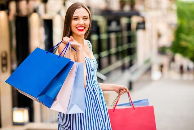 Donna felice in abito estivo in posa con le borse della spesa