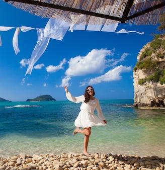 Donna felice in abito bianco estivo sulla spiaggia. ragazza caucasica che si rilassa e si gode la pace in vacanza.