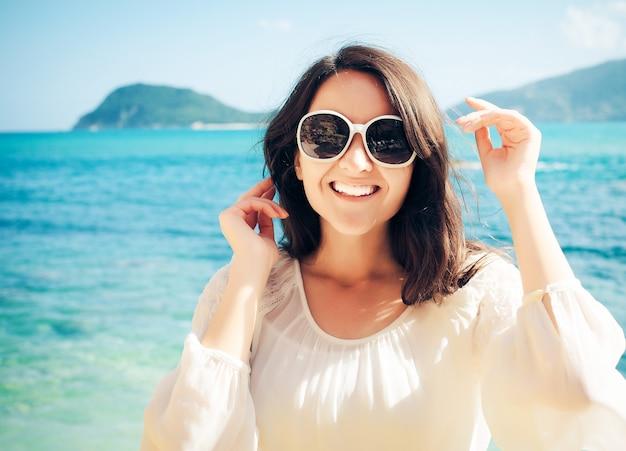 Donna felice in abito bianco estivo sulla spiaggia