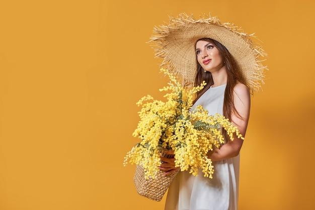 Donna felice in abito bianco estivo cappello di paglia con mazzo di fiori in borsa