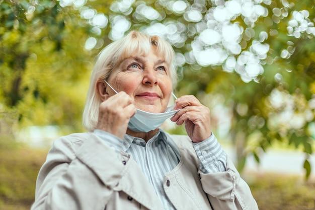 La donna felice si toglie la maschera medica protettiva dal viso godendosi la natura e il fresco