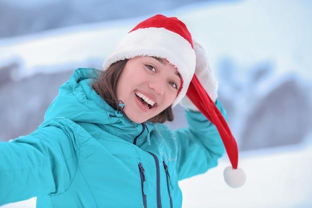 Donna felice che prende selfie al resort innevato. vacanze invernali