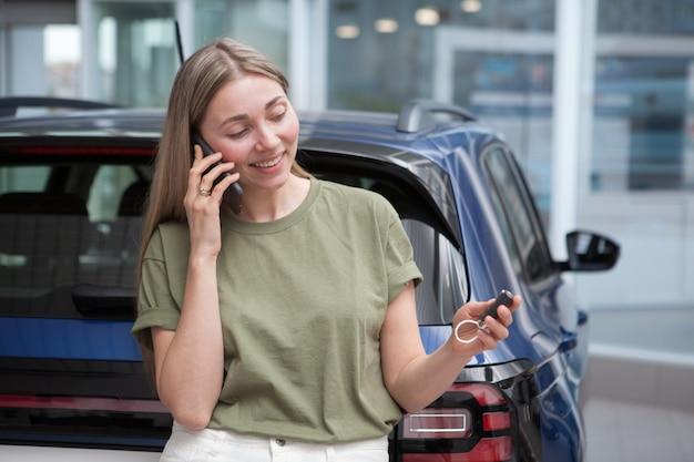 Donna felice che parla al telefono dopo aver acquistato una nuova automobile presso una concessionaria di auto